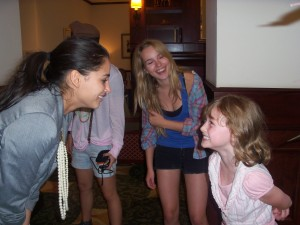 "Naomi Scott ""Mo"" has a staring contest with Zoe Hughes (LM author Mark Peter Hughes's 8 yr old daughter) as Bridgit Mendler ""Olivia"" looks on"