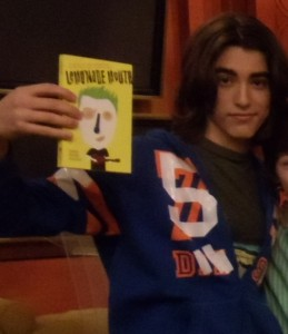 "Blake Michael holding up the book ""Lemonade Mouth"""